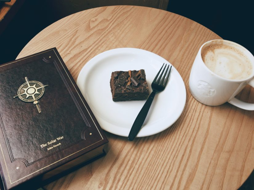Book, caramel brownie, and latté, on a coffee table