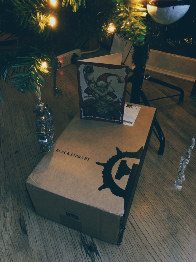 A cardboard box, with the Black Library logo on it, underneath a Christmas Tree